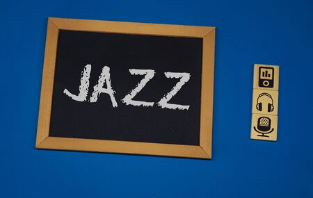 inscription JAZZ on a black board with a blue background with three wooden cubes