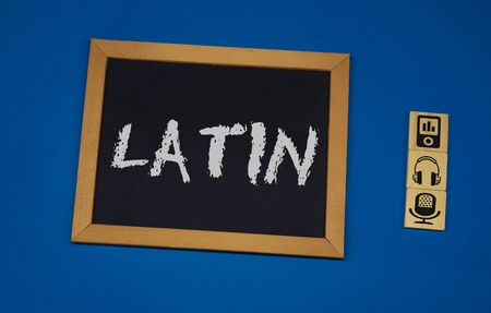 inscription LATIN on a black board with a blue background with three wooden cubes