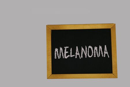 a sign lying on a gray background with the inscription melanoma