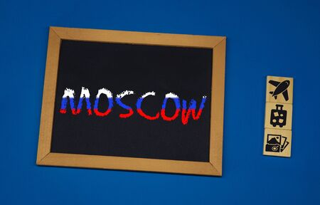 inscription MOSCOW on a black board with a blue background with three wooden cubes