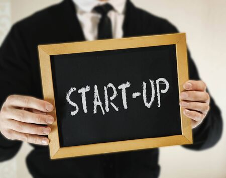 male businessman in a suit with tie holds in his hand a sign with the inscription START-UP
