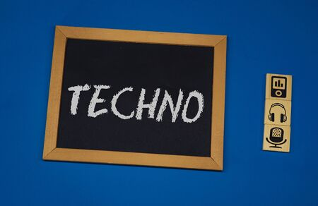 inscription TECHNO on a black board with a blue background with three wooden cubes Banco de Imagens