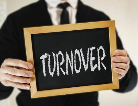 male businessman in a suit with tie holds in his hand a sign with the inscription TORNOVER