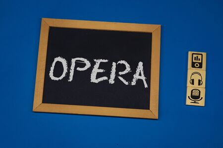 inscription OPERA on a black board with a blue background with three wooden cubes