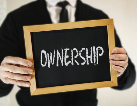 male businessman in a suit with tie holds in his hand a sign with the inscription OWNERSHIP