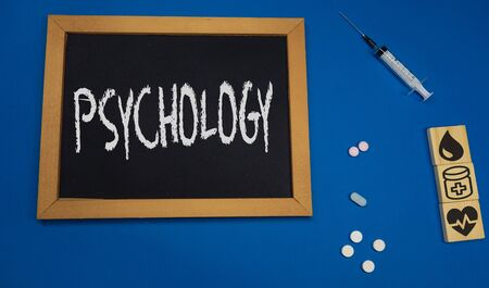 wooden tablet on blue medical table with the word PSYCHOLOGY
