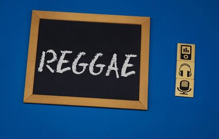 inscription REGGAE on a black board with a blue background with three wooden cubes