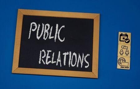inscription PUBLIC RELATIONS on a black board with a blue background with three wooden cubes
