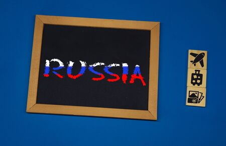 inscription Russia on a black board with a blue background with three wooden cubes