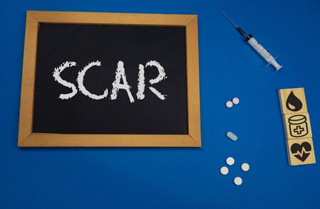 wooden tablet on blue medical table with the word SCAR Banco de Imagens