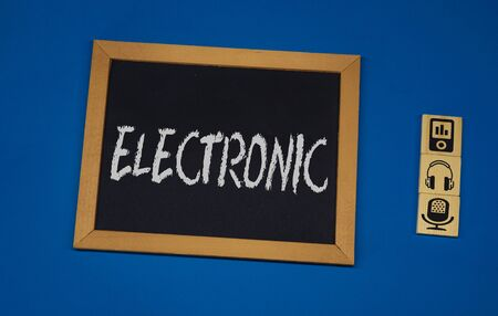 inscription ELECTRONIC on a black board with a blue background with three wooden cubes