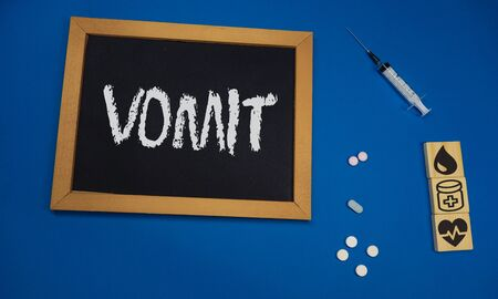wooden tablet on blue medical table with the word VOMIT