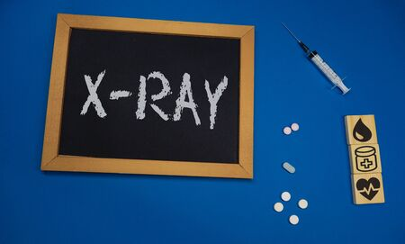 wooden tablet on blue medical table with the word X-RAY