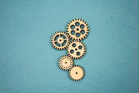 wooden gears lying on a blue background as a single mechanism.