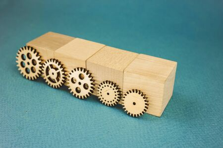 5 wooden gears standing leaning on wooden cubes