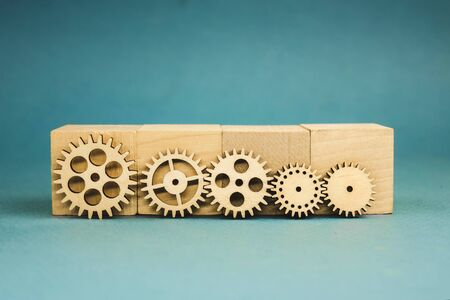 5 wooden gears standing leaning on wooden cubes.