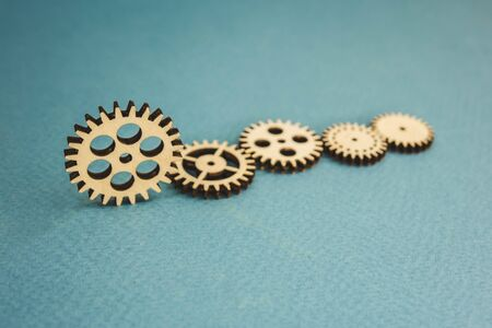 five wooden gears standing on a blue background.