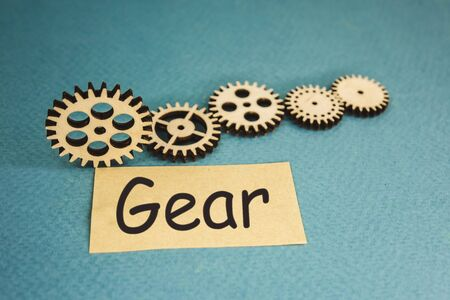 wooden gears lying on a blue background and the inscription gear.