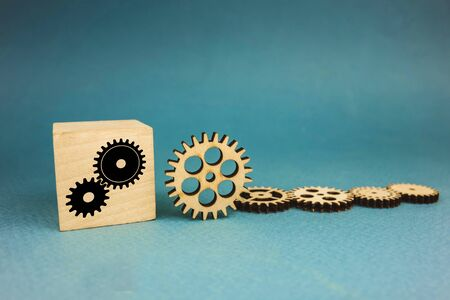 five wooden gears and one gear on a cube on a blue background
