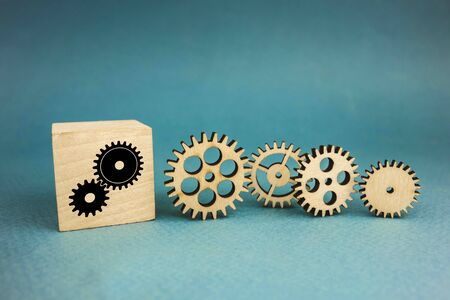 four wooden gears and one gear on a cube on a blue background