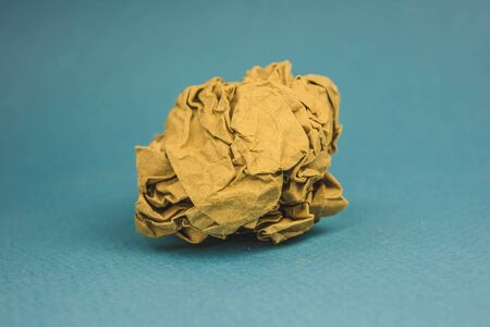 a piece of crumpled brown paper on a blue background. Stok Fotoğraf