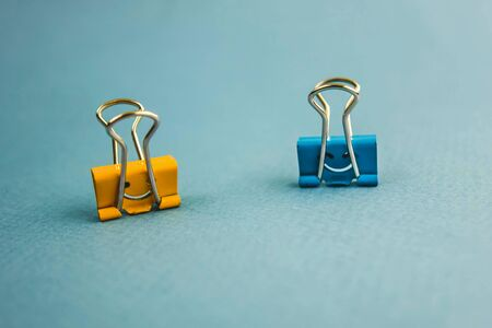 two paper clips in blue and orange with a smiley face on a blue background.