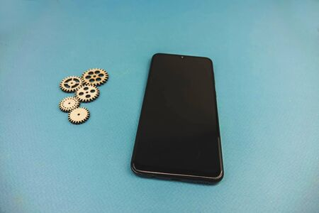 phone lying on a blue background and a pack of gears.