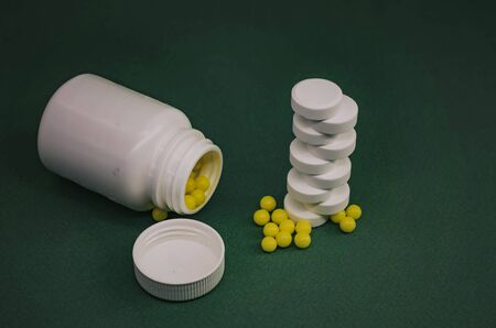 vitamins and tablets standing on a green background