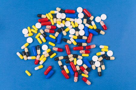 heap of multicolored tablets scattered on a blue background