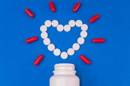 heart of white tablets on a blue background Stock Photo