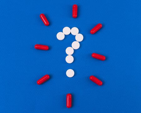 question mark laid out of white tablets on a blue background
