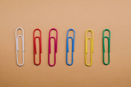 paper clips of different colors lying at the same distance from each other on a brown background
