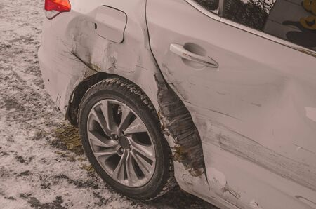 the white car was badly damaged after the accident. Фото со стока