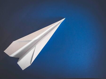 paper white aircraft lying on a blue background.