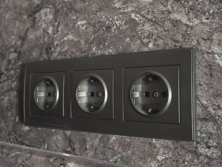 three dark black rosettes in a dark marble wall