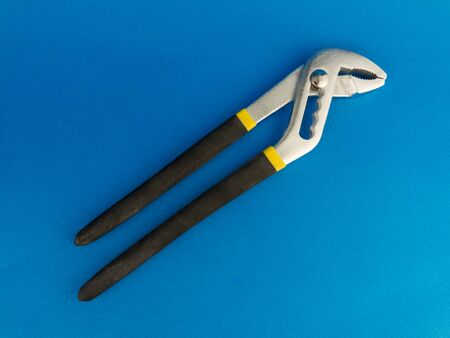 hand wrench lying on a blue background.