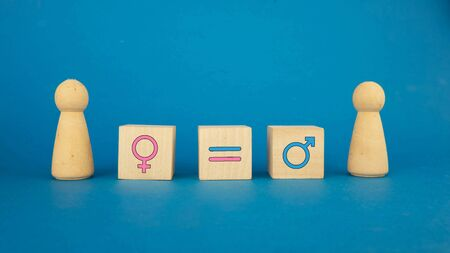 the concept of equality between a man and a woman on wooden cubes