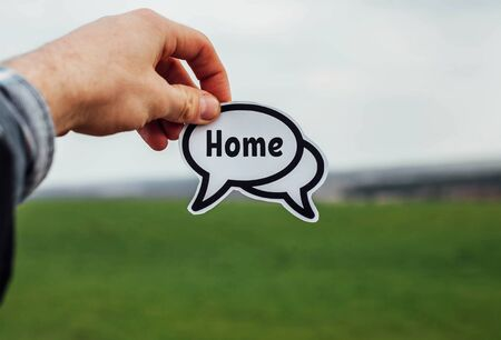 word home in the hand of a man standing in a field.