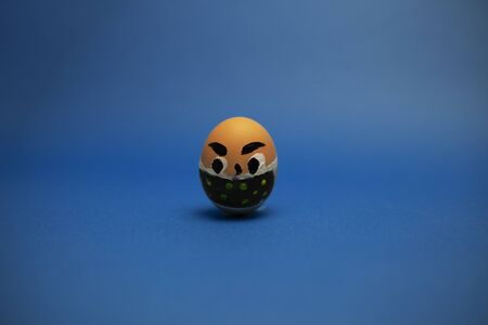 one egg with eyes and a mask on a blue background. Stock fotó