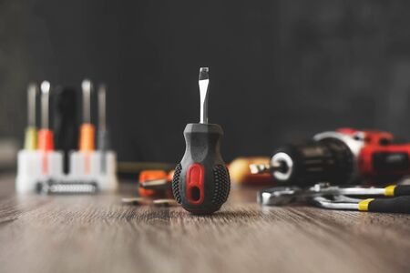 a small screwdriver set among the tools on a wooden table. 스톡 콘텐츠