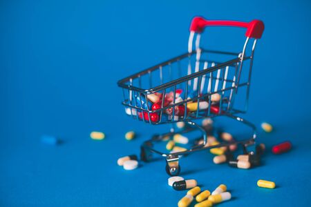 Red basket with a bunch of pills on a blue background. 스톡 콘텐츠