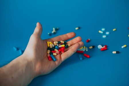 a bunch of different pills in a man's hand on a blue background.