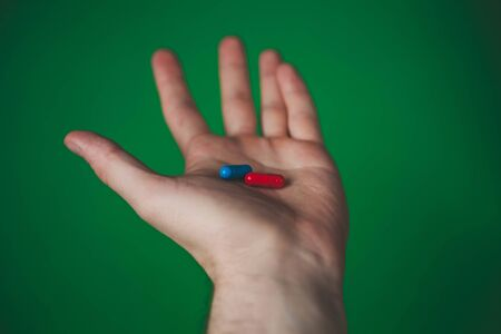 red and blue tablet in a man hand on a green background.