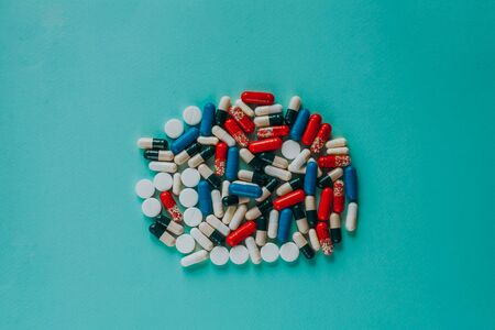 one big pile of colorful pills on a blue background