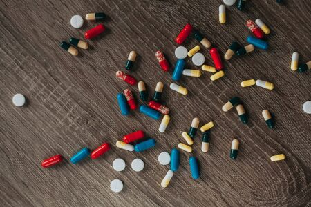 pile of pills on a wooden table. 스톡 콘텐츠