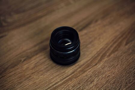 camera lenses on a wooden table top view. background and workspace for photography.