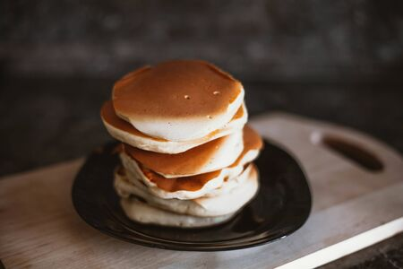 a stack of neat pancakes on a wooden stand.
