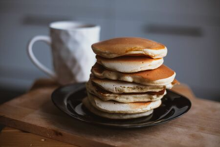 a Cup of coffee and a stack of pancakes on the table. 스톡 콘텐츠
