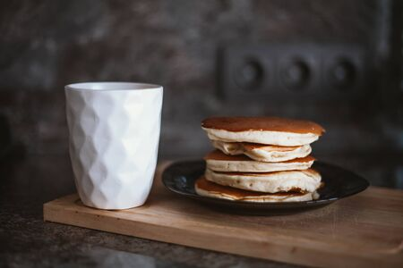 a white mug and a stack of pancakes on a plate.