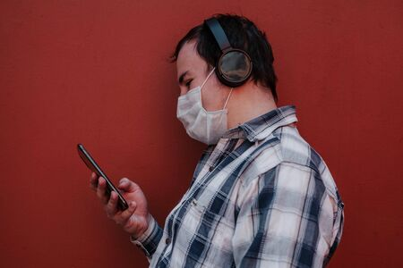 the masked man uses the phone leaning against the wall.